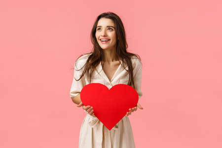 Amused and carefree good-looking european female in dress, holding valentines card, big red heart, looking left amazed and happy, smiling impressed, standing pink background joyful