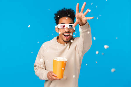 So realistic I want touch it. Entertained and amused happy african-american hipster guy in movie, wearing 3d glasses extend hand and throwing popcron to grab animated thing, blue background