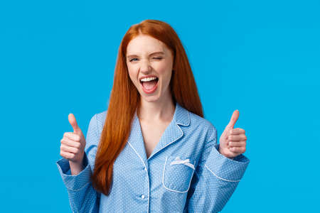 You go girl, women power. Encouraged and optimistic good-looking redhead woman in nightwear assure everything awesome, promote great product, show thumbs-up in like or approval, wink