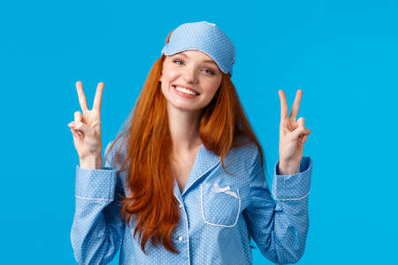Silly and cute young redhead caucasian girl in sleep mask and nightwear, wearing lovely pyjama feeling alright, showing peace gestures and smiling, ready for sweet dreams, blue background