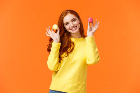 Girlfriend want share dessert, holding two macarons and smiling, suggest bite with lovely grin, tilt head flirty, standing happy orange background, enjoy winter holidays and sweet gifts