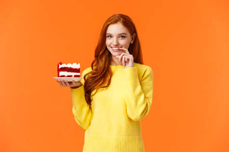 Girl wants share her piece cake with loved one. Romantic silly cute girlfriend brink piece dessert to eat together, smiling and touching lip flirty, eating junk food during diet, orange background