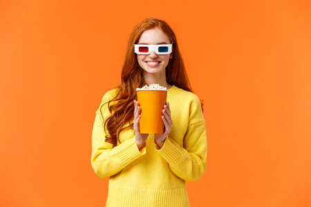 Girl anticipate start of movie, smiling excited, visit cinema, holding popcorn and grinning, wear 3d glasses to watch new fantasy film, like watching premiere in theatre on big screen, orange wall