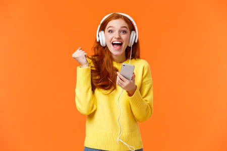 Hooray yes new song. Attractive cheerful and excited redhead woman fist pump in joy and positive emotions, wearing headphones, holding smartphone, smiling camera happily, orange background
