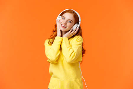 Waist-up portrait cute teenage redhead girl in white headphones, tilt head listen music, touch earphones and smiling camera, singing along favorite song, standing orange background