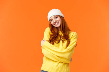 Winter is her favorite season. Tender silly and lovely redhead girl embrace herself and tilt head, smiling cute, wearing beanie and soft warm sweater just for cold weather, orange background