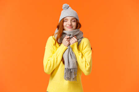 Cute and happy redhead woman walking along winter holidays fair market, close eyes and smiling as smelling something delicious, wearing warm grey hat and scarf, standing orange background