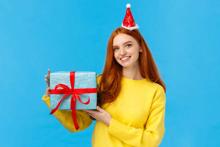 Waist-up portrait young cute redhead caucasian female celebrating christmas holidays, new year party, exchanching gifts with friends during secret santa, holding box of present, wear fancy hat