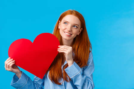 Dreamy romantic teenage girl thinking how give valentines card to lover, smiling lovely and looking up thoughtful. Attractive redhead woman in nightwear, holding heart and grinning, blue background Reklamní fotografie - 138202095