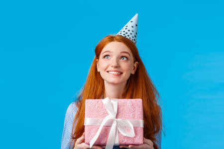 Cheerful dreamy girl imaging whats inside birthday box. Cute redhead glamour teenager in b-day cap, receive lovely present, holding gift and looking upper left corner happy and thoughtful. Reklamní fotografie - 138202405