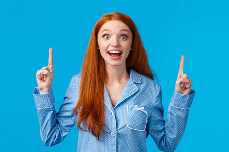 Excited cute redhead girl in nightwear smiling amused and fascinated, telling about incredible choices, great opportunity, pointing fingers up staring camera dreamy and amazed, blue background Reklamní fotografie - 138202107