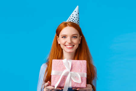 Waist-up portrait cheerful happy, pretty redhead, ginger girl celebrating birthday, receive cute pink wrapped present, wearing b-day cap and smiling, having fun at party, blue background Reklamní fotografie - 138202068