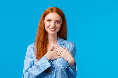 Feminine lovely redhead woman with long ginger hair, wearing pyjamas, hold hands on heart and smiling tenderly, having something precious hidden inside soul, standing blue background Reklamní fotografie - 138202420