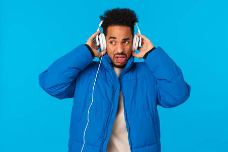 Cringing and bothered african-american man grimacing hearing bad sound quality of headphones, dont like song take-off earphones and making unsatisfied expression, disgusted blue background