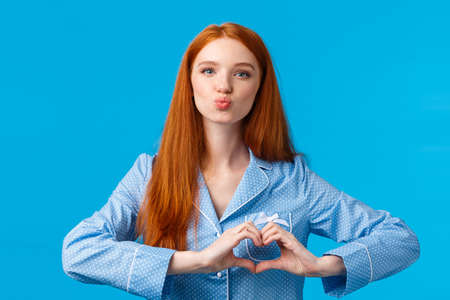 Lovely sensual good-looking redhead female with long ginger hair, freckles, folding lips for kiss showing heart love gesture over chest, wearing nightwear, ready sleep, blue background Reklamní fotografie - 138202407