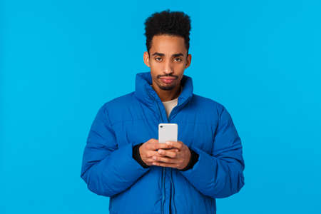 Upset and disappointed bothered african american young guy missed chance, feeling unhappy and moody, sulking frowning holding smartphone, standing padded winter jacket blue background