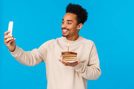 Celebration and holidays concept. Cheerful african american guy addicated social media, sharing memory with online followers, holding b-day cake with candle, taking selfie, celebrate birthday.