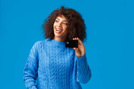 Cheerful attractive african-american woman with afro haircut, winter sweater, talking to friend looking left, smiling pleased, showing credit card, paying without cash, standing blue backgroun Archivio Fotografico