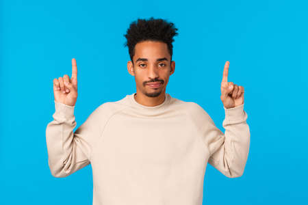 Unimpressed, skeptical good-looking modern african-american hipster male with afro haircut, moustache, pointing fingers up, looking unbothered and careless, dont like presents, blue background Stock fotó