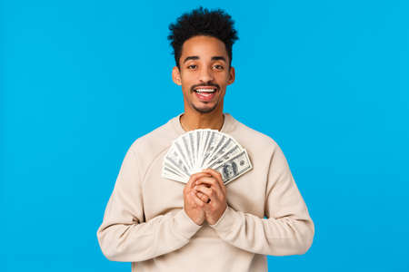 Delight, satisfaction and love concept. Happy and relieved ecstatic african-american guy winning huge money, holding cash, lottery prize and smiling pleased, dreaming buy car, blue background