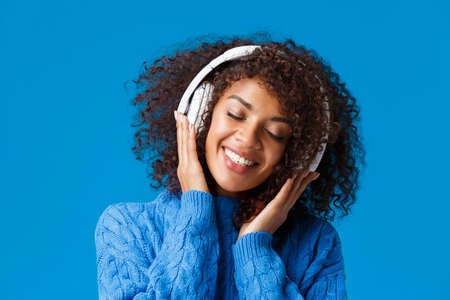 Close-up portrait happy smiling, romantic and tender african american woman enjoying listening music in headphones, tilt head close eyes dreamy and grinning delighted, blue background 免版税图像