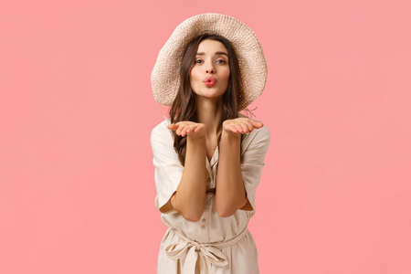 Tenderness, glamour and romance concept. Elegant good-looking feminine woman in hat and dress, folding lips silly blowing air kiss and sending it you with palms, giving love, pink background