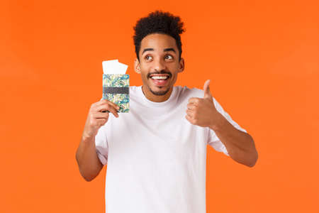 Happy enthusiatic attractive african-american hipster guy enjoying holidays abroad, show thumb-up smiling and looking up, holding passport, win two tickets luxury resort, orange background