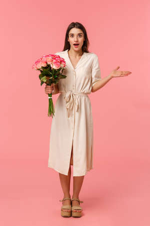 Full-length vertical portrait surprised see boyfriend with flowers, receive charming bouquet, spread hand sideways and shrugging surprised, look wondered and astonished, standing pink background Stock fotó