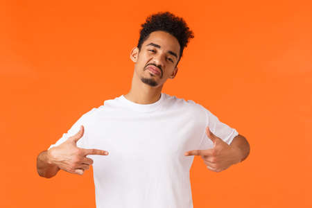 Sassy and confident assertive african-american man, acting cool and cheeky, pointing himself proud, boastful standing orange background, show-off, making impression, wearing white t-shirt