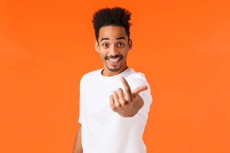 Excited friendly, smiling and happy african american hipster guy, male model luring someone, stretching hand and waving finger to come closer, inviting person, found candidate, orange background
