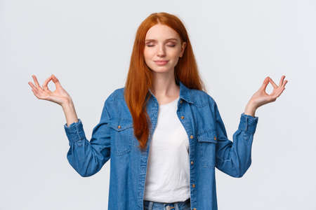 Patience, zen and modern lifestyle concept. Peaceful, calm and relieved happy smiling redhead woman meditating, hold hands sideways in lotus pose, practice yoga, white background 스톡 콘텐츠