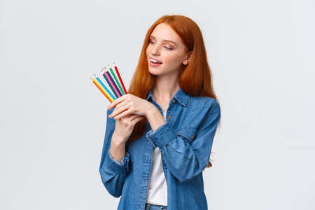 Creative and skilful good-looking redhead female in denim shirt, picking colored pencils, smiling thinking what draw, creating artworks, standing white background thoughtful