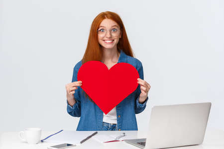 Cheerful and excited cute girlfriend with red hair, cant wait give big red valentines heart to boyfriend, showing sympathy, confess in love, celebrating lovers day, standing white background