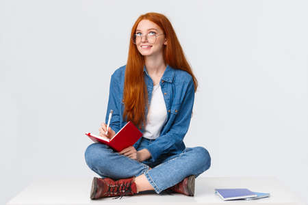 Dreamy and creative cute diligent female student with red hair, in glasses, sitting on floor with legs crossed surrounded by notebooks writing something, creating poem, look up thoughtful