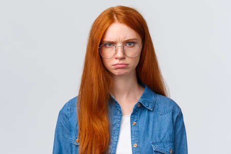 Close-up portrait strict and angry, mad gloomy redhead girl staring offended and disappointed, pouting frowning outraged, condemn something, look skeptical and bothered white background
