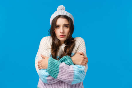 Turn on heater please its freezing. Upset and gloomy young silly girl in winter hat, sweater, trembling from low temprature, hugging herself warm-up, hate cold season, blue background