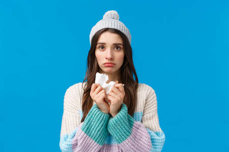 Upset young woman feelings unwell, have fever, sick on winter holidays, wearing hat and sweater, holding napkin sneeze and have runny nose, looking sad camera, caught cold or flu, blue background Stock Photo