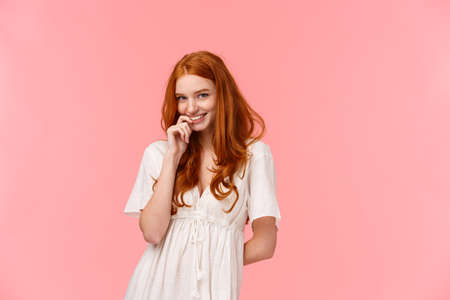Romance, relationship and tenderness concept. Beautiful tender redhead woman in cute white dress, blushing and giggle silly, smiling biting finger gazing at camera sensual, flirt over pink background