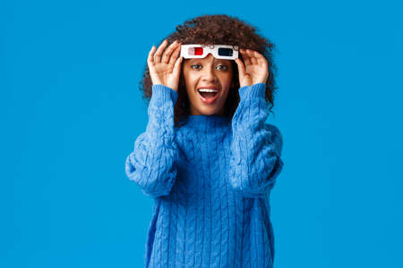 Excited happy and cheerful young woman watching movie in 3d glasses, laughing and checking screen without eyewear, impressed with cinematics and awesome special effects, standing blue background
