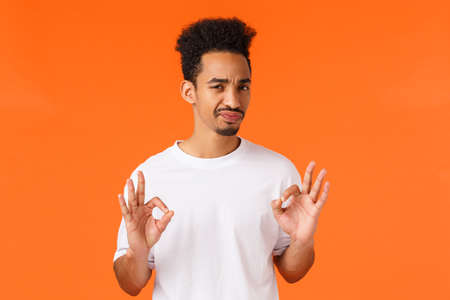 Not bad. Skeptical and unimpressed young african-american guy with moustache, smirk and grimacing showing alright gesture, feeling reluctant agree do job but unwilling, orange background