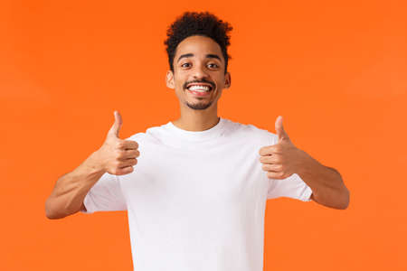 Optimistic, enthusiastic african-american male in white t-shirt, fully agree, feeling happy and satisfied, had great vacation, give positive feedback awesome hotel, showing thumbs-up in approval Stockfoto
