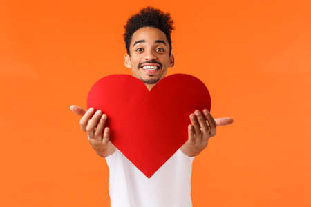 Guy giving his love you. Handsome lovely african-american man stretching hands and presenting red heart, smiling, showing true love and sympahy, express affection, standing orange background