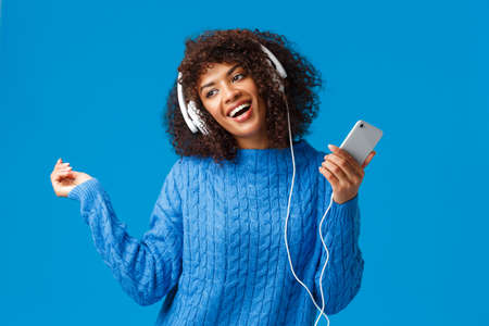 Joyful and carefree lovely african-american female model in winter sweater, dancing to rhythm music, listening new track on song app, christmas playlist, wear headphones hold smartphone Stock Photo