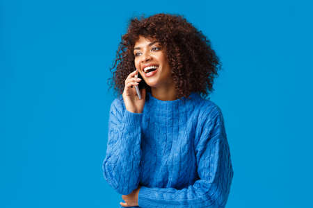 Charismatic attractive happy african-american woman answering phone, laughing happily and smiling, holding smartphone near ear, standing blue background joyful, wishing happy holidays