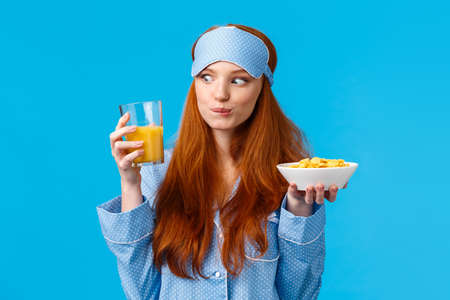 Carefree good-looking caucasian pretty foxy girl, college student smiling amused staring at orange juice glass, holding cereals, eating morning meal, breakfast, standing blue background Archivio Fotografico