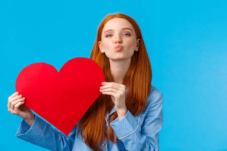 Tenderness, relationship and valentines day concept. Caring and romantic cute foxy teenage girlfriend holding red heart card and folding lips, blowing kiss, give mwah, blue background Фото со стока - 138434128