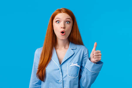 Wow that was awesome. Impressed speechless young redhead girl saw stunning trick or performance, heart amazing story showing thumb-up, staring breathtaking, folding lips astounded Stock Photo