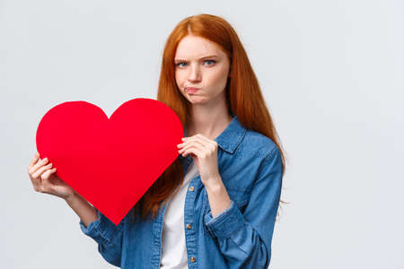 Serious-looking troubled, unsure cute redhead girl thinking what gift buy in addition to valentines day big red heart card, plan romantic date, pouting and frowning camera perplexed