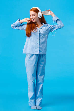 Full-length vertical shot cheerful and upbeat, carefree redhead teenage girl dancing and enjoying beautiful morning, wearing nightwear skipping college stay home listen music in headphones