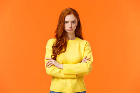 I am mad. Offended sulky cute and timid redhead curly girl, cross arms chest, sulking angry and tensed, frowning stare disappointed someone sad rude words, standing orange background insulted